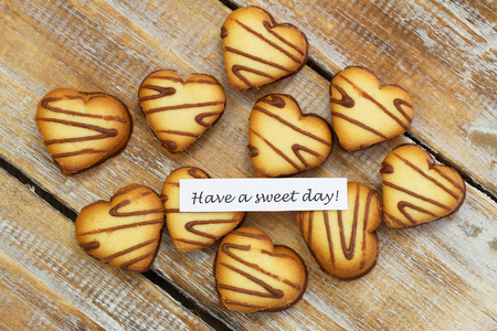 scattered in heart shaped: Have a sweet day card with heart shaped cookies on rustic wood Stock Photo