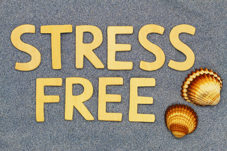 stress free: Stress free written with wooden letters on blue sand