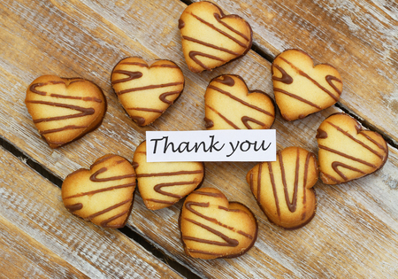 scattered in heart shaped: Thank you card with heart shaped cookies on rustic wood