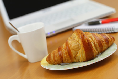 office desk: Butter croissant and coffee on office desk Stock Photo