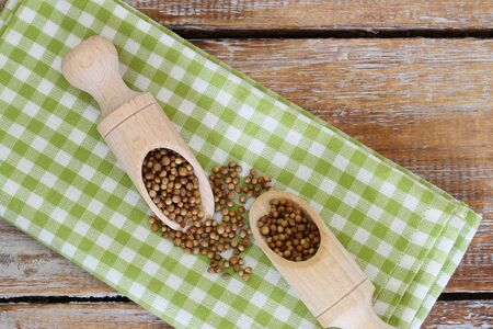 coriander seeds: Coriander seeds on wooden scoops on checkered cloth