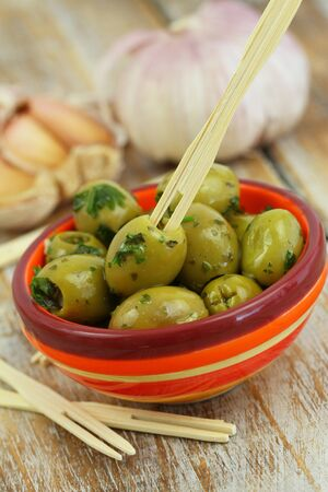 Green olives with garlic in traditional clay bowl, closeup
