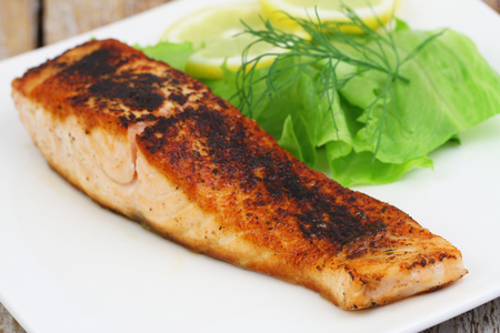 side salad: Grilled salmon with green side salad on white plate Stock Photo