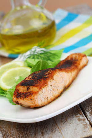 side salad: Grilled salmon with lemon and side salad on white plate