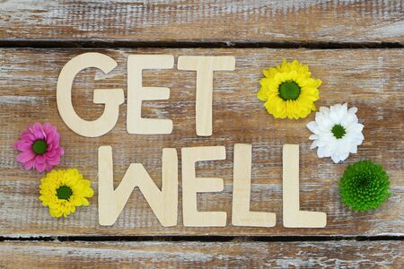 get well: Get well written with wooden letters on rustic wood Stock Photo