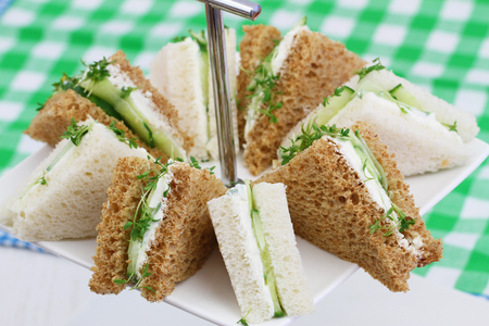 english cucumber: White and brown cream cheese and cucumber sandwiches on cake tray