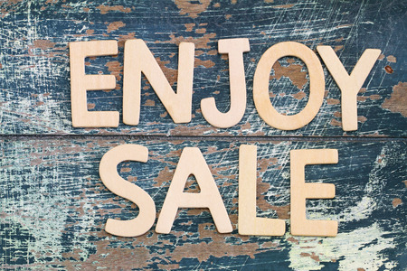 written: Enjoy sale written with wooden letters on rustic surface