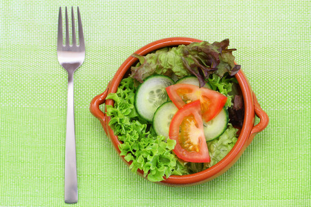 salade verte: Green salad in clay bowl on place mat