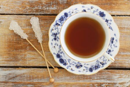 wood stick: Vintage tea in porcelain cup and two sugar sticks on rustic wooden surface