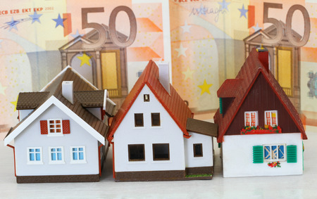 repayment: Model houses with Euro banknotes in the background Stock Photo