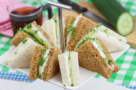tea time: White and brown cream cheese and cucumber sandwiches on cake stand