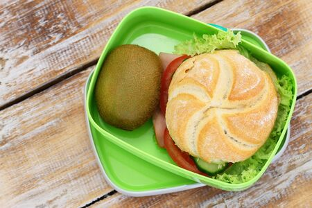 healthy lunch: Lunch box with ham roll and kiwi fruit