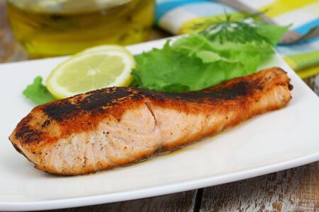 side salad: Grilled salmon on white plate with side salad and lemon Stock Photo