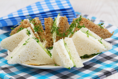english cucumber: Traditional white and brown cream cheese and cucumber sandwiches and checkered napkins
