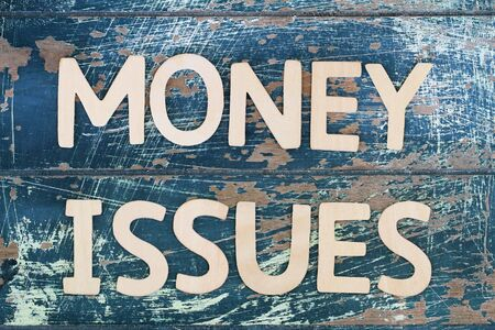 money issues: Money issues written on rustic wooden surface
