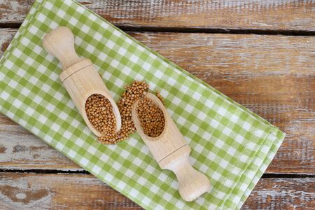 indian mustard: Mustard seeds on wooden scoops on checkered cloth Stock Photo