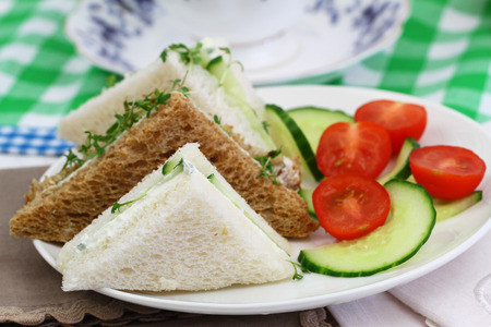 salade verte: White and brown cream cheese and cucumber sandwiches with green salad Banque d'images