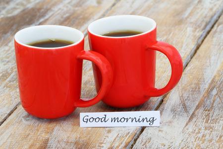 taza: Buena tarjeta de la ma�ana con dos tazas de caf� rojas en la superficie de madera r�stica