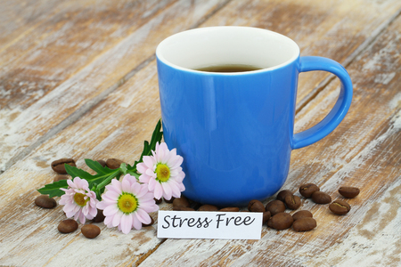 stress free: Cup of coffee on rustic wooden surface with note saying stress free