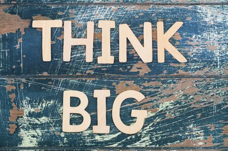 think big: Think big written on rustic wooden surface