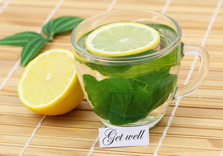 get well: Get well card with mint tea and lemon on bamboo mat Stock Photo