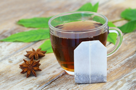 tea bag: Tea bag leaning against cup of tea and anise
