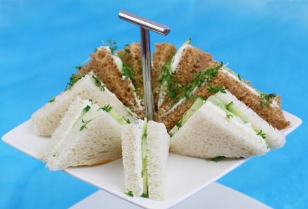 english cucumber: White and brown cream cheese sandwiches on cake tray Stock Photo