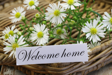 welcome home: Welcome home card with chamomile flowers on wicker tray Stock Photo
