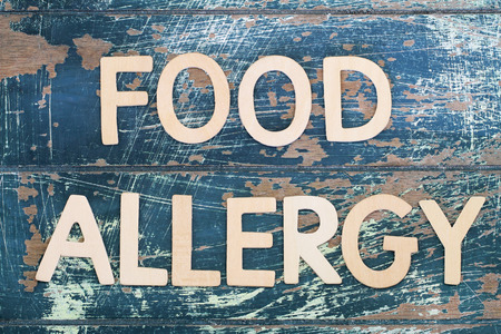 food allergy: Food allergy written on rustic wooden surface Stock Photo