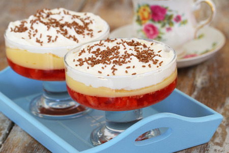 trifle: Traditional strawberry trifle dessert with fresh whipped cream and sprinkled with chocolate on wooden tray Stock Photo