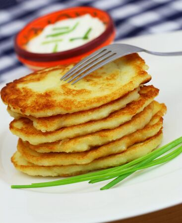 stacked up: Potato fritters stacked up on white plate with bowl of sour cream