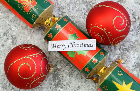 christmas cracker: Merry Christmas card with red baubles and Christmas cracker