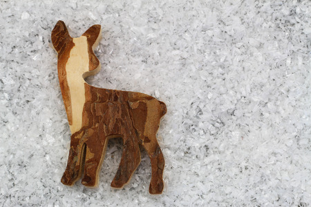 copyspace: Wooden roe deer on snowy surface with copyspace Stock Photo