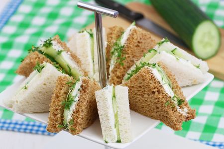 english cucumber: White and brown cream cheese and cucumber sandwiches Stock Photo