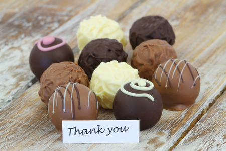 dark chocolate: Thank you card with assorted chocolates, truffles and pralines on rustic wooden surface