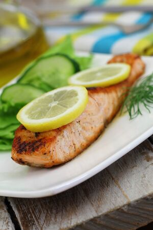 side salad: Grilled salmon with slices of lemon and green side salad