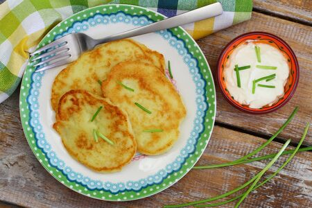 spring onions: Potato fritters garnished with spring onions and bowl of sour cream on rustic wooden surface