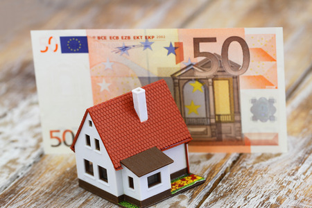 banco dinero: Modelo de casa en frente de cincuenta billetes en euros en la superficie de madera r�stica Foto de archivo