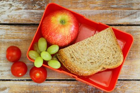 almuerzo: caja de almuerzo con el emparedado marrón pan, manzana roja, uvas y tomates cherry