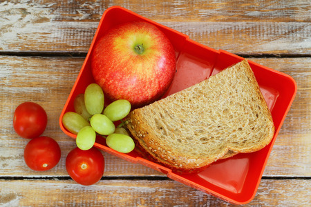 healthy lunch: Lunch box with brown bread sandwich, red apple, grapes and cherry tomatoes Stock Photo