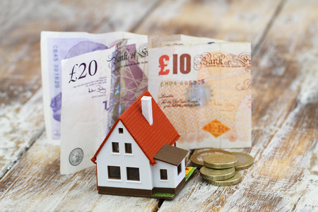 model house: Model house in front of British pound notes and coins