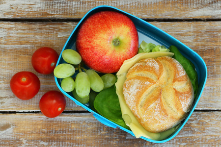 lunch meal: School lunch box Consisting cheese roll, red apple, grapes and cherry tomatoes Stock Photo