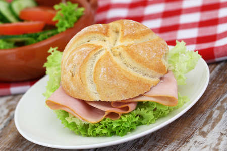 Bread roll with ham and lettuce on white plate, closeup