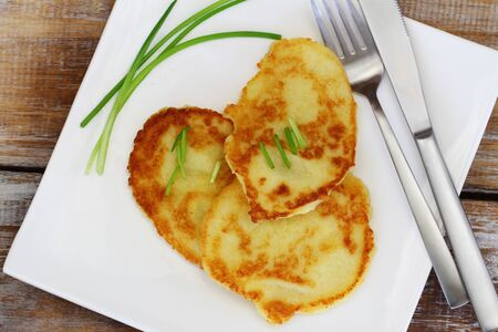 garnished: Potato fritters garnished with spring onions on white plate on rustic wooden surface