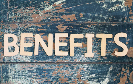 dole: Become benefits written with wooden letters on rustic surface