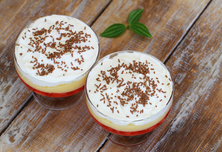 trifle: Traditional desserts trifle with fresh whipped cream and sprinkled with chocolate on rustic wooden surface