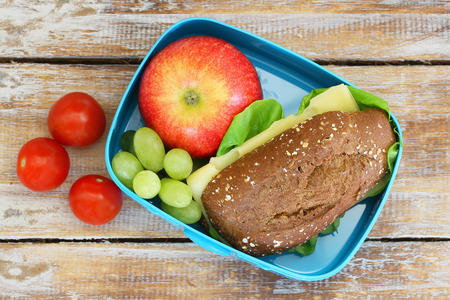 healthy lunch: Lunch box Consisting of wholegrain cheese sandwich, apple, grapes and cherry tomatoes Stock Photo