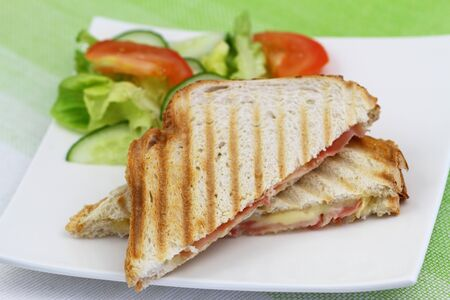 english cucumber: Toast with ham and cheese and green salad on white plate