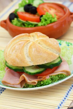 side salad: Lunch Consisting of ham roll with lettuce, tomato and cucumber and green side salad Stock Photo