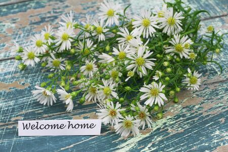 welcome home: Welcome home card with fresh chamomile flowers on rustic wooden surface